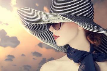Fashion women in wide hat at sunrise