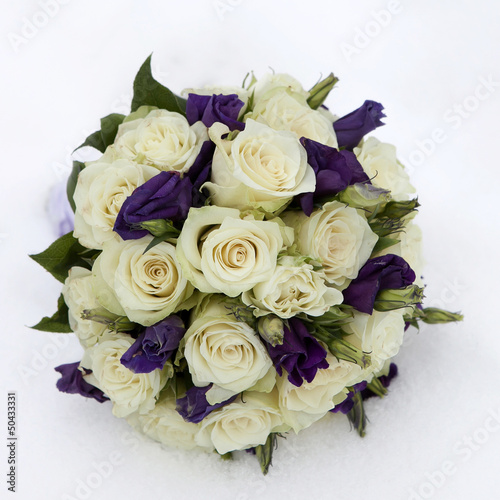 wedding bouquet with rose and lisianthus lying on snow