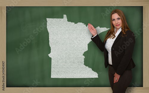 Teacher showing map of minnesota on blackboard