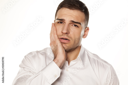 a young man with a toothache on white background