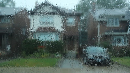 Rainstorm in the suburbs. Car drives by.