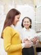 woman helps the girl in choosing bridal accessories