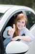 glückliche frau im auto zeigt daumen hoch