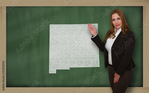 Teacher showing map of new mexico on blackboard