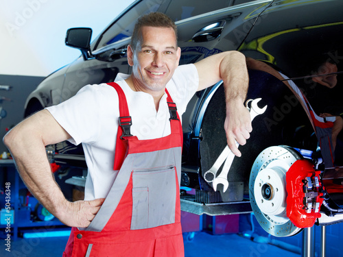 Smiling motor mechanic shows his work tools in front of a brake