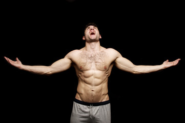 Topless man shouting with his arms outstretched