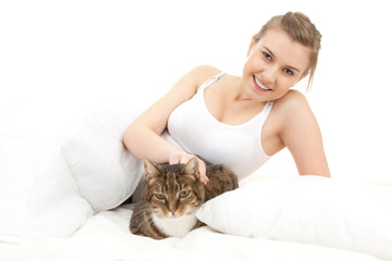 smiling young woman relaxing in white bedding