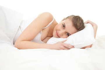 beautiful young woman lying in white bedding