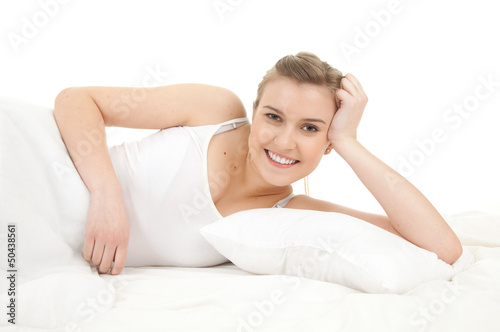 smiling beautiful girl relaxing in white bedding