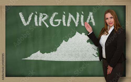 Teacher showing map of virginia on blackboard