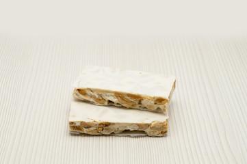 Pieces of Christmas hard almond turron on white background