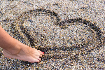 Young Girl Drawing A Heart In The Sand