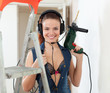 Sexy woman in headphones with drill