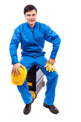 Young construction worker sitting on his toolbox