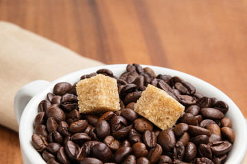 heap of coffee beans in cup with cane-sugar