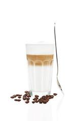 latte macchiato mit stehendem löffel und kaffeebohnen