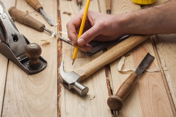 carpenter working,hammer,meter and chisel  over wood table