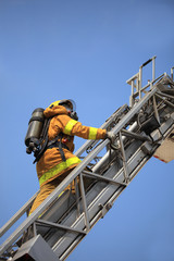 Firefighter ascends upon a one hundred foot ladder.