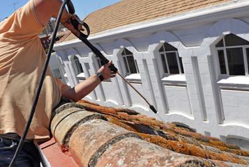 Trabajador limpiando un tejado