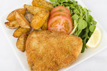Wiener Schnitzel - Breaded fried veal, potato wedges and salad.
