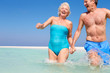 Senior Couple Having Fun In Sea On Beach Holiday
