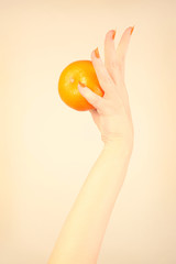 Hand mandarin with orange nails manicure