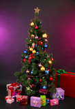 Decorated Christmas tree with gifts on dark color background