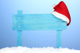 Wooden road sign with Santa hat on blue background