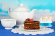 Teapot, cup of tea and delicious cake on blue natural