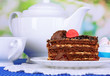 Teapot, cup of tea and delicious cake on natural background