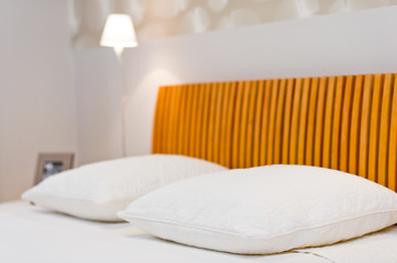 Comfortable soft pillows on the bed with lamp in the background