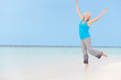 Senior Woman Jumping On Beautiful Beach