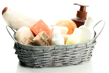 Composition of cosmetic bottles and soap in basket, isolated