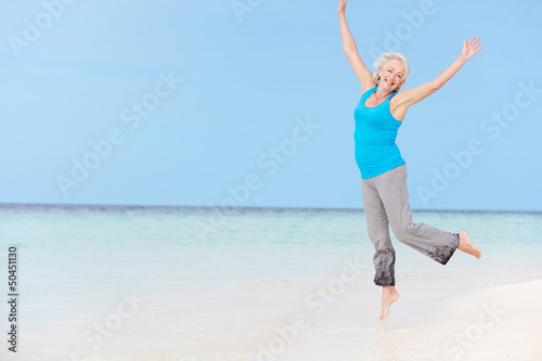 Senior Woman Jumping On Beautiful Beach