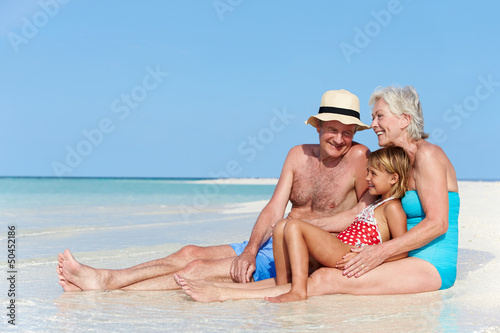 Grandparents With Granddaughter Enjoying Beach Holiday