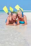 Senior Couple With Snorkels Enjoying Beach Holiday