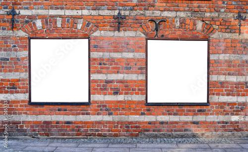 Empty billboards on brick wall