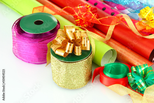 Rolls of Christmas wrapping paper with ribbons, bows isolated
