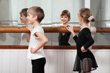 children standing at ballet barre