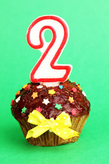 Birthday cupcake with chocolate frosting on background