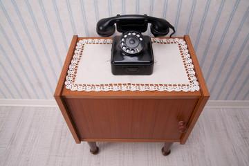 telefono nero a disco classico su mobiletto vintage
