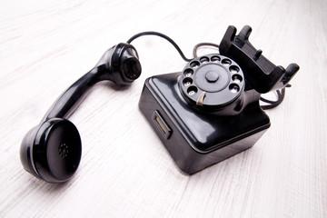 telefono nero a disco vecchio stile su fondo chiaro