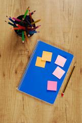 Cuaderno y lápices de colores en un bote