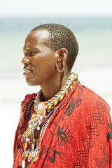 Portrait of young Massai man on bright beach, with narrow focus