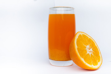 glass with orange juice and orange on a white background
