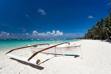 Wooden boat on tropical beach with white sand