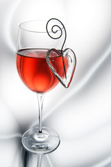 Glass of red wine decorated heart.