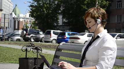 Business woman talking through a headset, sitting on a bench