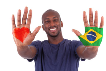Brazilian man hands with a painted heart and  brazilian flag, i