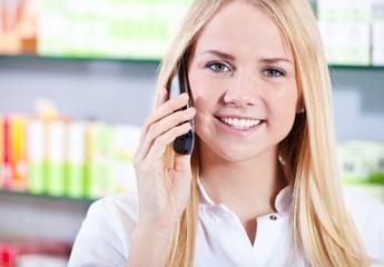 Verkäuferin im Einzelhandel führt Telefonat